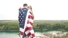 Happy couple hugging wrapped in an american flag in nature. Independence day, lifestyle, travel concept. Happy couple hugging wrapped in an american flag in stock footage