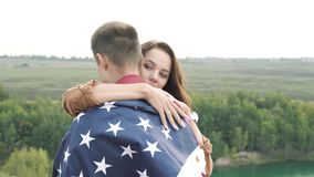 Happy couple hugging wrapped in an American flag in nature. Independence Day, lifestyle, travel concept. Happy couple hugging wrapped in an American flag in stock video