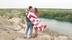 Happy couple hugging wrapped in an American flag in nature. Independence Day, lifestyle, travel concept. Happy couple hugging wrapped in an American flag in stock video footage