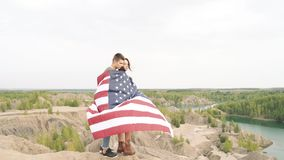 Happy couple hugging wrapped in an American flag in nature. Independence Day, lifestyle, travel concept.  stock footage