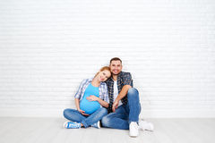 Happy couple husband and pregnant wife near blank  brick wall Royalty Free Stock Photos