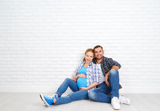 Happy couple husband and pregnant wife near blank  brick wall Stock Photography