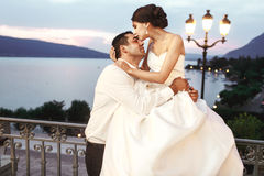 Happy couple husband and wife hugging at balcony in evening near Stock Images