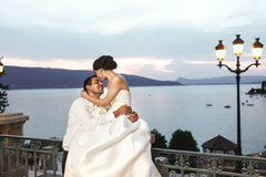 Happy couple husband and wife hugging at balcony in evening near Stock Photos