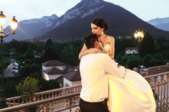 Happy couple husband and wife hugging at balcony in evening near Stock Photo
