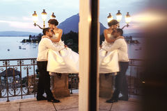 Happy couple husband and wife hugging at balcony in evening near Stock Image