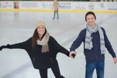 Happy couple ice skating outdoors stock images