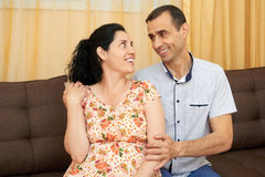 Happy couple indoor, pregnant woman and man, beautiful people portrait, sit on sofa Stock Images