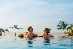 Happy couple in infinity pool stock image