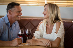 Happy couple interacting with each other while having glass of wine. In restaurant Stock Images