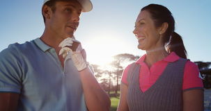 Happy couple interacting with each other while playing golf stock footage