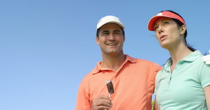Happy couple interacting with each other while playing golf stock video footage