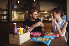 Happy couple interacting while fast food Royalty Free Stock Photography