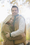 Happy couple in jackets hugging in park Royalty Free Stock Images