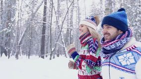 Happy couple jogging in the forest on a winter day. Happy couple jogging together in the forest on a winter day. Slow motion stock footage