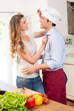 Happy couple joking while cooking Stock Photos