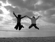 Happy Couple Jumping. Young couple are so happy, in love royalty free stock image