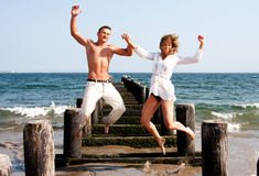 Happy couple jumping. Cute happy couple smiling jumping playfully at the beach with a pier and the ocean water in the background heaving fun Stock Photos