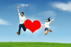 Happy couple jumping against blue sky. Happy asian couple jumping with a huge heart cutout Royalty Free Stock Photography