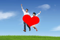 Happy couple jumping against blue sky. Happy asian couple jumping with a huge heart cutout Stock Image