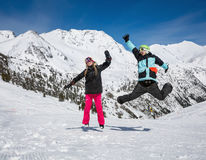 Happy couple jumping in mountains. Happy couple jumping on the background of snowy mountains Stock Image
