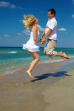 Happy couple jumping on the beach. Happy couple jumping on the sunny beach Royalty Free Stock Photography