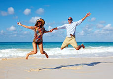 Happy couple jumping on the beach. Crazy vacation Stock Image