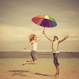 Happy couple jumping on the beach. At the day time Stock Image