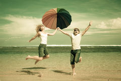 Happy couple jumping on the beach. At the day time Royalty Free Stock Image