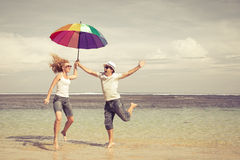 Happy couple jumping on the beach Royalty Free Stock Photos