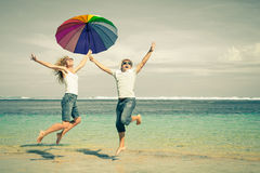 Happy couple jumping on the beach. At the day time Royalty Free Stock Photography