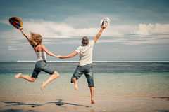 Happy couple jumping on the beach. At the day time Royalty Free Stock Photos