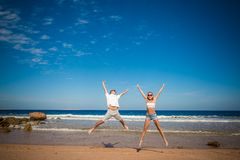 Happy couple jumping. On the beach excited Stock Image