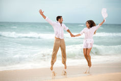 Happy couple jumping on beach. Fun on tropical vacation Stock Images