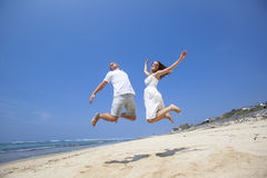 Happy couple jumping on beach Royalty Free Stock Photography