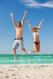 Happy couple jumping on the beach. Picture of happy couple jumping on the beach Royalty Free Stock Images