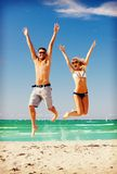 Happy couple jumping on the beach. Picture of happy couple jumping on the beach Royalty Free Stock Photo