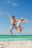 Happy couple jumping on the beach. Picture of happy couple jumping on the beach (focus on man Royalty Free Stock Image