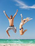Happy couple jumping on the beach. Picture of happy couple jumping on the beach (focus on man Stock Photos