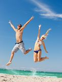 Happy couple jumping on the beach Royalty Free Stock Photography