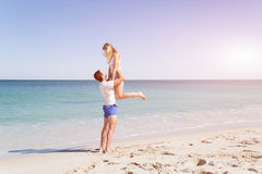 Happy couple  jumping on beach vacations. Travel concept of young couple cheering for summer holidays on beach Stock Image