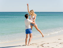Happy couple  jumping on beach vacations. Travel concept of young couple cheering for summer holidays on beach Royalty Free Stock Photo