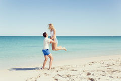 Happy couple  jumping on beach vacations. Travel concept of young couple cheering for summer holidays on beach Stock Photography