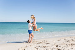 Happy couple  jumping on beach vacations. Travel concept of young couple cheering for summer holidays on beach Royalty Free Stock Photography