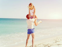 Happy couple  jumping on beach vacations. Travel concept of young couple cheering for summer holidays on beach Royalty Free Stock Image