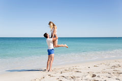 Happy couple  jumping on beach vacations. Travel concept of young couple cheering for summer holidays on beach Royalty Free Stock Photos