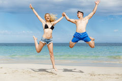 Happy couple  jumping on beach vacations. Travel concept of young couple cheering for summer holidays on beach Stock Photos