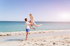 Happy couple  jumping on beach vacations. Travel concept of young couple cheering for summer holidays on beach Royalty Free Stock Images