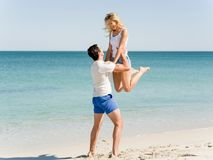 Happy couple  jumping on beach vacations. Travel concept of young couple cheering for summer holidays on beach Stock Photo