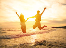 Happy couple jumping on beach. Young happy couple jumping on beach Royalty Free Stock Photos